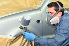Worker painting silver car. Royalty Free Stock Photo