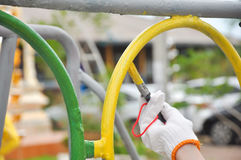 Worker painting steel tube with paint brush Stock Photo