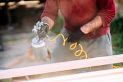 worker painting timber with spraygun, airgun. Carpentry details stock photography