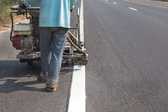 Worker painting traffic line with spraying eject machine. Stock Images