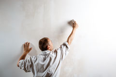 Worker painting wall with brush in white color. Copy space. Royalty Free Stock Photo