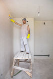Worker painting wall with painting roller Royalty Free Stock Images