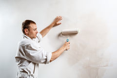 Worker painting wall with roller in white color. Copy space. Professional worker painting wall with roller in white color. Copy space Stock Image