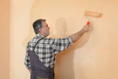 Worker painting wall in a room Royalty Free Stock Image