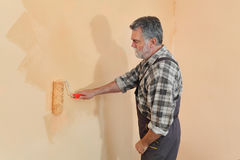 Worker painting wall in a room Royalty Free Stock Images