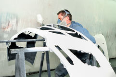 Worker painting white car bumper. Royalty Free Stock Photos
