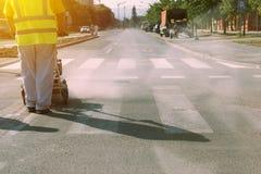 Worker is painting zebra pedestrian crosswalk Stock Photography