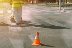 Worker is painting zebra pedestrian crosswalk Royalty Free Stock Images