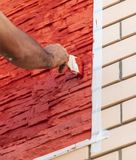 A worker paints a brick house with red paint.  stock photo