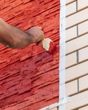 A worker paints a brick house with red paint.  royalty free stock photos