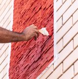 A worker paints a brick house with red paint.  stock photos