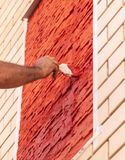 A worker paints a brick house with red paint.  royalty free stock photography