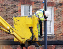 Worker paints a street lamp Stock Photography