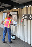Worker paints wall of elevated subway platform Royalty Free Stock Photography