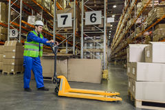 Worker with pallet truck posing. Male worker wearing blue uniform jacket and hardhat driving pallet truck towards pallets with boxes Stock Images