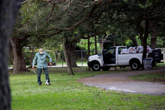 Worker. Park and Recreation cleaning up the park. View of trash and truck in the background Stock Photo