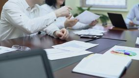 Worker passing diagram to colleagues at corporate meeting, good company results stock footage