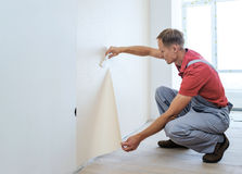Worker pasting wallpapers. He presses for better adhesion using scraper Stock Image