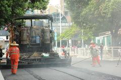 Worker Pavement construction in China ,Asia. The workers are carrying out road construction using large machine equipment in China ,Asia Royalty Free Stock Photography