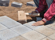 The worker paves a stone path Royalty Free Stock Image