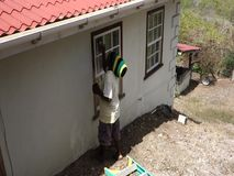 A worker performing maintenance on a house in the tropics. A man preparing window ledges for varnishing in the caribbean stock video