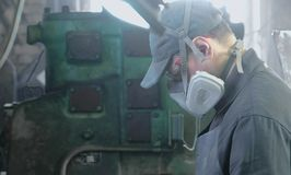 Worker performs his job in a protective mask on his face in the shop among the equipment. Worker performs his job in a protective mask on his face in the shop royalty free stock images