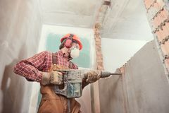 Worker with demolition hammer breaking interior wall. Worker with personal protection equipment and demolition hammer at service for interior brick wall stock images