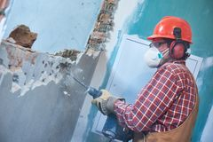 Worker with demolition hammer breaking interior wall royalty free stock photo