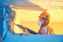Worker with demolition hammer breaking interior wall stock photos