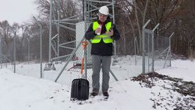 Worker with phone and thermos near snow shovel and fence stock video