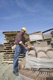 Worker Picking A Tile At Site Royalty Free Stock Photography