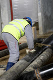 Worker with pipes. Worker working with pipes on construction site in Romania Royalty Free Stock Photography