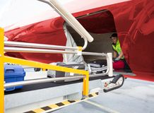 Worker Placing Baggage On Conveyor While Unloading Airplane Royalty Free Stock Photography