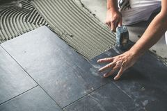 Worker placing ceramic floor tiles on adhesive surface. Leveling with rubber hammer stock image