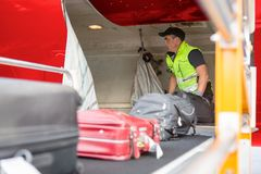Worker Placing Luggage On Conveyor To Unload Airplane. Mature male worker placing luggage on conveyor to unload airplane royalty free stock photography