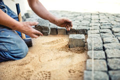 Worker placing stone tiles in sand for pavement, terrace. Worker placing granite cobblestone pavement at local terrace. Construction worker placing stone tiles Stock Photography