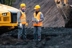 Worker with a plan and a clipboard discussing things in quarry. Worker with a plan and a clipboard discussing super important things in quarry royalty free stock photo