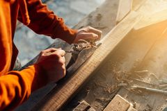 A worker planes a wooden bar with a plane royalty free stock images