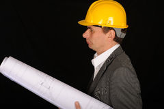 Worker with plans. Worker with yellow hardhat is holding blueprints over black background Royalty Free Stock Photography