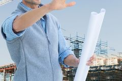 Worker with plans at construction site. Digital composite of engineer at construction Stock Photo