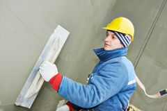 Worker at plastering facade work. Builder at facade plastering work during industrial building with putty knife float Stock Image