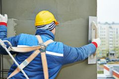 Worker at plastering facade work. Builder at facade plastering work during industrial building with putty knife float Royalty Free Stock Image