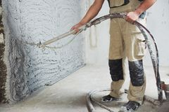 Plastering the interior wall with an automatic spraying plaster pump machine royalty free stock photos