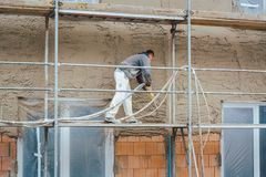 Worker plastering outer wall of newly built house stock photo