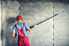 Worker with plastering tools renovating a house. builder worker plastering facade industrial building with leveler Stock Image
