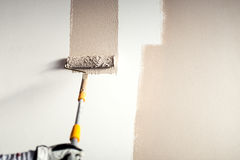 Worker plastering a wall, painting with paint brush decoration on interior walls. Professional worker plastering a wall, painting with paint brush decoration on Stock Photo