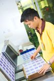 Worker of plastic cards factory prepares lamination Stock Photos