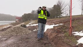 Worker with plastic pipe talking on cell phone near the trench. In winter day stock video footage