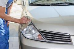 The worker polishes optics of headlights Stock Image