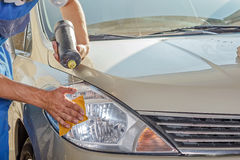 The worker polishes optics of headlights Stock Photo
